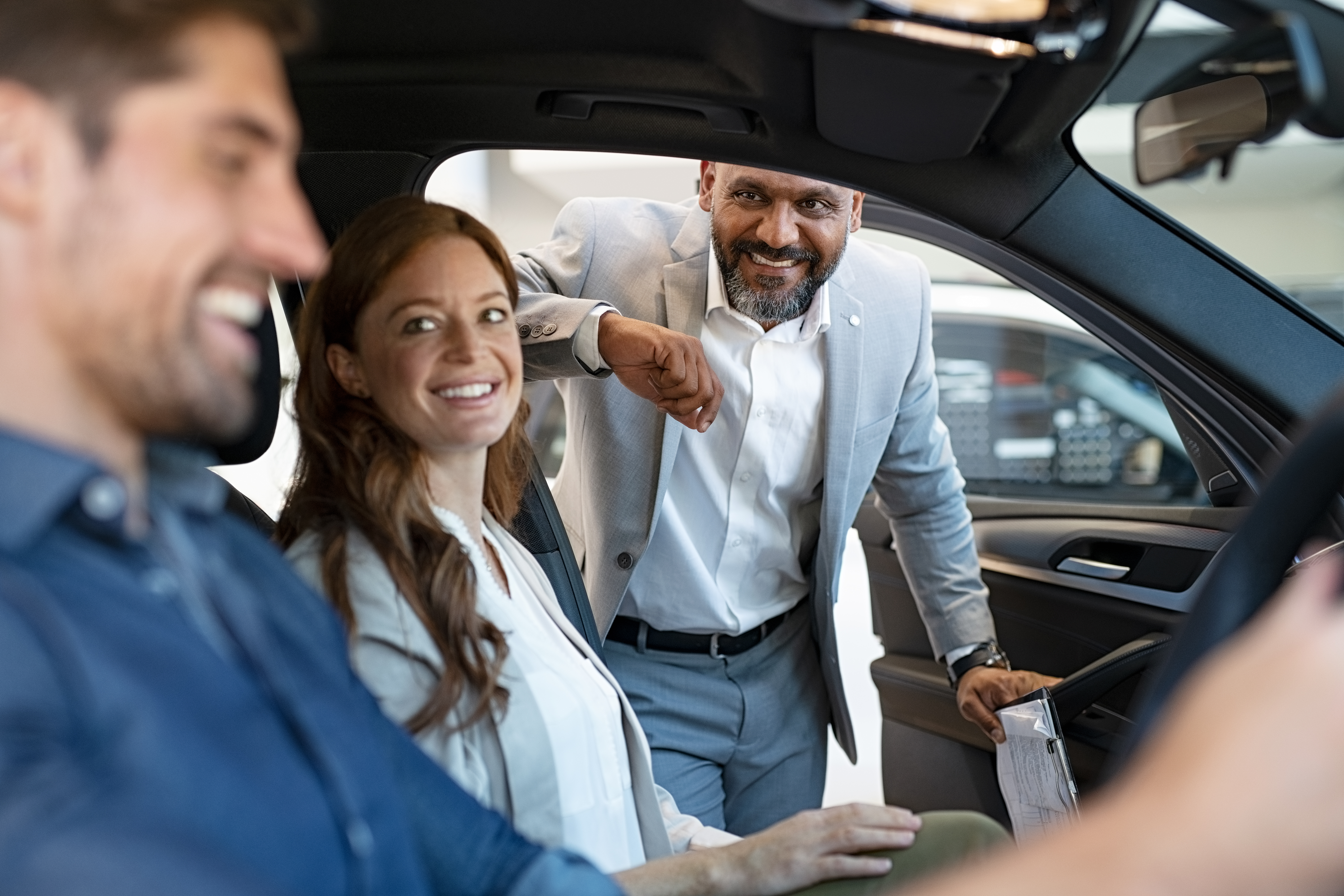 Salesman Showing New Car To Couple LCUSVAD