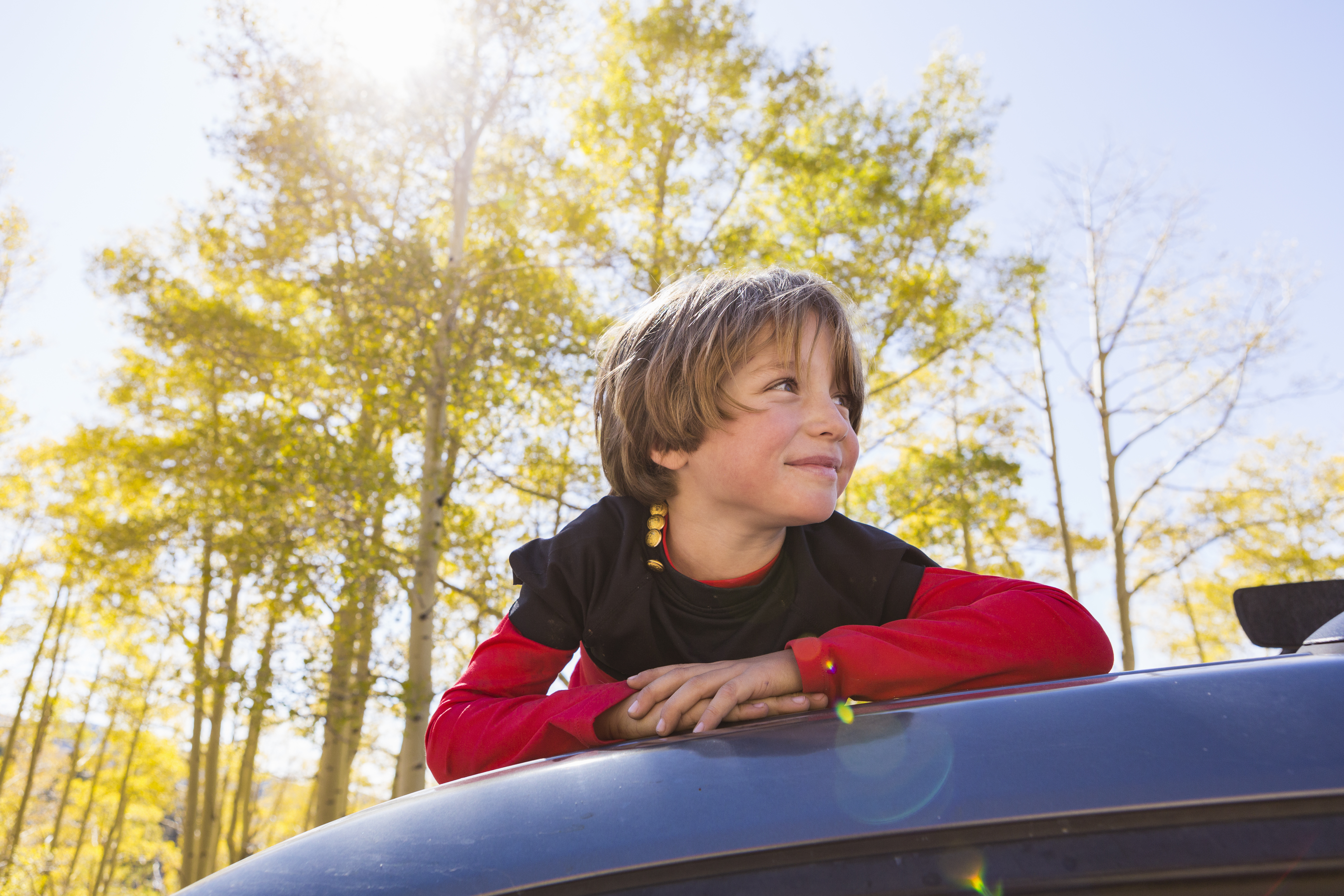 A Smiling 6 Year Old Boy Lying On The Hood Of A Bl FVTGSRT